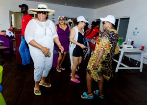 Moments at Mr Biodun Awosika's 60th birthday beach party showing guests dancing.
